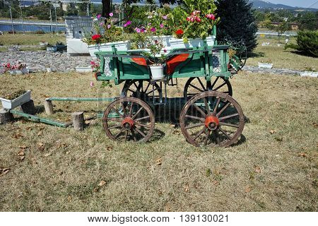 Wagon covered with flowers in the yard in Monastery St. John the Baptist, Kardzhali,  Bulgaria