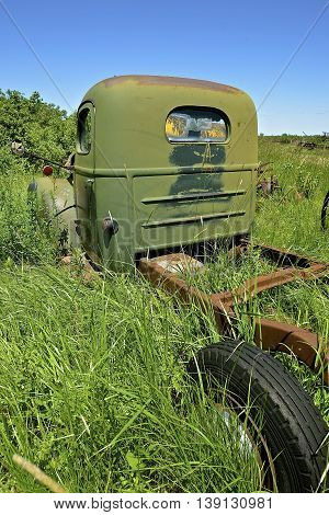 An old green truck from the 50's era is left parked  in long grass  and exposes the chassis, cab, and one tire.