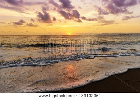 Ocean sunset is a beautiful ethereal seascape with magenta colored clouds and a glistening sun setting on the horizon.