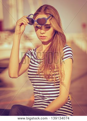 Summer fashion. Portrait girl in blue heart shaped sunglasses enjoying summer breeze at sunset in marina