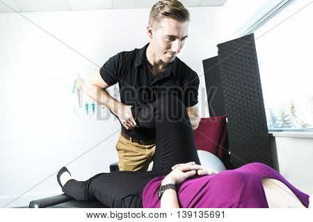 A Male Osteopath Treating Female Patient With Hip Problem