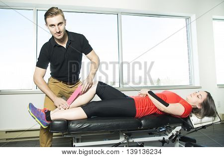 A Physiotherapist using tape in medical office