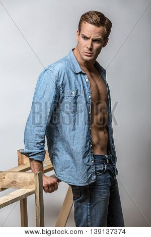 Muscular guy in a blue denim unbuttoned shirt and blue jeans stands in the studio on the gray background. He looks to the side while leans on a wooden construction. Vertical.