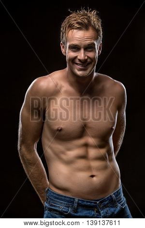 Man with a smile looks into the camera on the black background in the studio. He stands in blue jeans with naked torso. Guy holds his hands behind the torso. Vertical low-key photo.