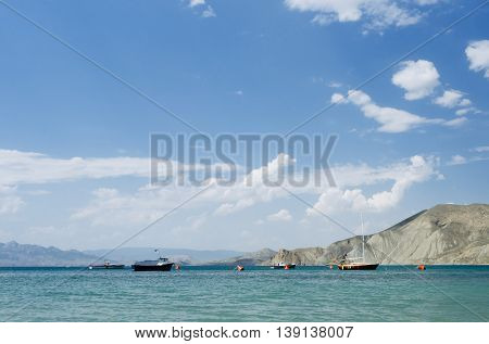 Summer sea resort. Blue sky with cumulus clouds. Sunny landscape with boats on the water. Mountains on the horizon