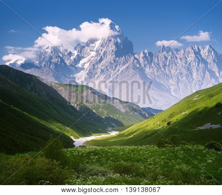 Mountain landscape with a river. Sunny summer day. Slopes with green grass and beautiful valley. Blue sky and the top of the clouds. Collage of two frames
