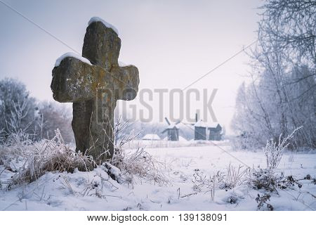 Old stone cross. Burial at the Museum of Folk Architecture and way of life Ukrainians. Winter landscape. Pirogovo museum, Kiev, Ukraine, Europe. Artistic style of photos processing. Color toning