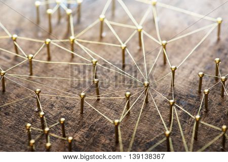 Linking entities. Network, networking, social media, internet communication abstract. Many small network connected to a larger network. Web of gold wires on rustic wood. . Shallow Depth of field.