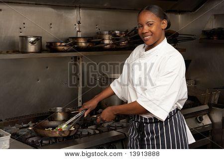 Female Chef Preparing Meal On Cooker In Restaurant Kitchen