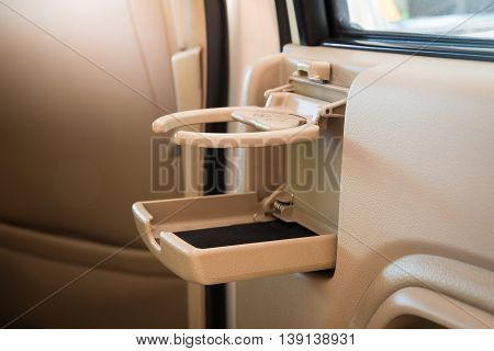 Place fo coffee or tea mugs or bottle on the vehicle console in modern luxury car interior