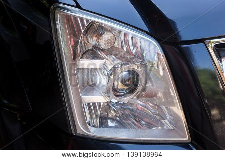 Closeup headlights of modern black car with projector lens