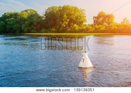 Summer water sunset landscape - trees along the bank of the river and buoy on the water under warm sunset light. Summer landscape natural view.