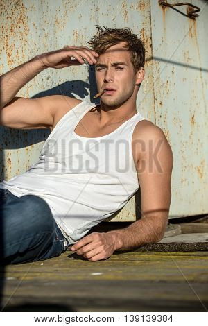 Cute guy in a white singlet and blue jeans lies on the industrial building. He smokes a cigarette. Man looks in front of himself and holds the right hand near his face. Outdoors. Vertical.
