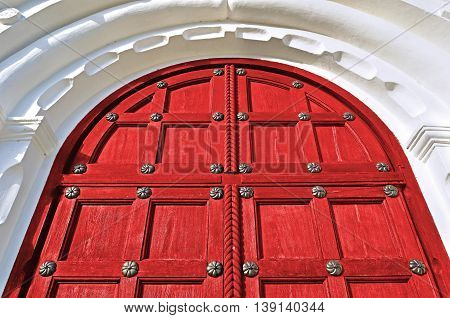 Architecture view. Architecture detailed background - aged wooden door of red color with metal rivets and upper arch of white stone - vintage architecture background
