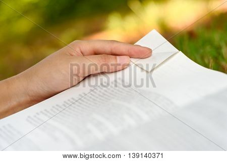 Woman's hand holding a book while folding down the corner of a page / dog-earing a book page.