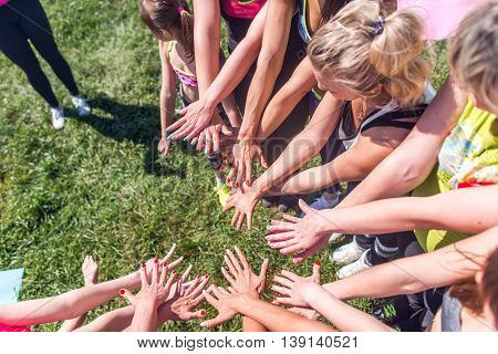 Group of women putting their beauty hands together stylish colorful nails art manicure.