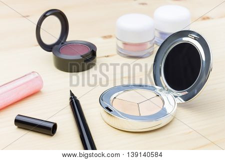 Woman cosmetics include eyes liner and lip gloss and eyeshadow and foundation or face powder on wood table
