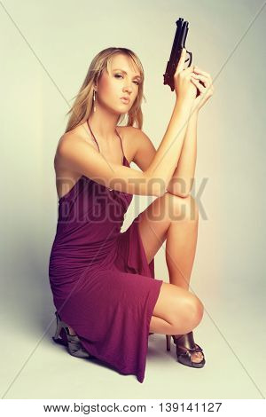 Beautiful young woman holding gun