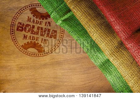 Round the stamp imprint of Made in Bolivia on a wooden surface.