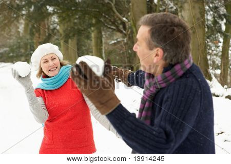 Senior Couple Having Snowball Fight In Snowy Woodland