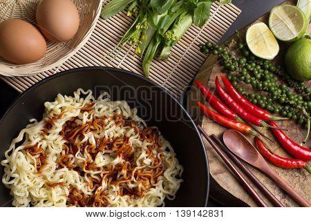 noodles in black bowl garnished on kitchen table