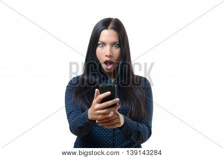 Young woman reacting in horror to a text message on her mobile phone standing staring at it with her mouth open in shock