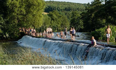 BATH UK - JULY 19 2016 People walking across and swimming in River Avon. Hundreds flock to Warleigh Weir 3 miles from Bath on the hottest day of the year.