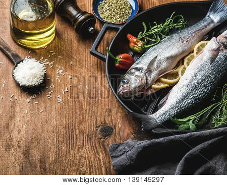 Ingredients for cookig healthy fish dinner. Raw uncooked seabass fish with rice, olive oil, lemon slices, herbs and spices on black grilling iron pan over rustic wooden background, top view, selective focus, copy space, horizontal composition