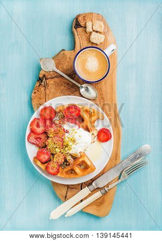 Breakfast set. Warm homemade belgium waffles with whipped cream, strawberry, maple syrup and crushed pistachios, cup of espresso and cubes of brown sugar on olive rustic wooden board over blue painted wooden background, top view, vertical composition