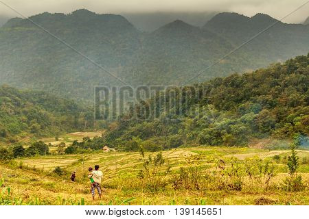 A woman holds a baby and surveys the fields and hills of the Vietnamese countryside