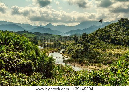 A river, rolling green hills, and distant mountains in the Vietnamese countryside