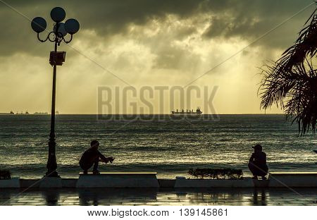 Two men squat and watch the ships on a beach as yellow moody sun rays break through the storm clouds in Vietnam