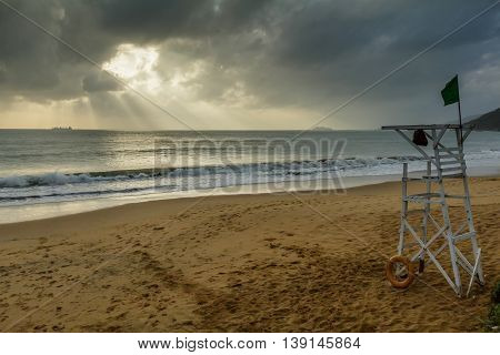The sun breaks through the storm clouds over a deserted beach in Vietnam
