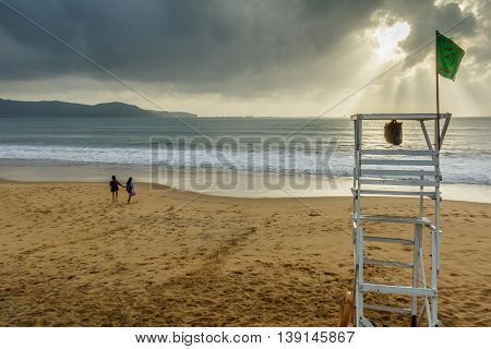 Two girls hold hands on a deserted beach on a stormy morning in Vietnam
