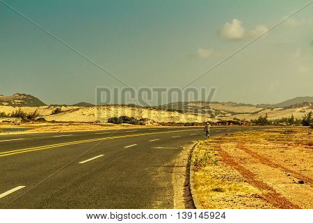 A Vietnamese woman walking along a deserted new highway through sand dunes in Vietnam