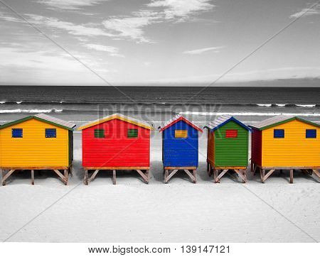 The row of wooden brightly colored huts on Sunrise Beach. Atlantic ocean. Cape Town. Muizenberg. South Africa. Modern architecture art.