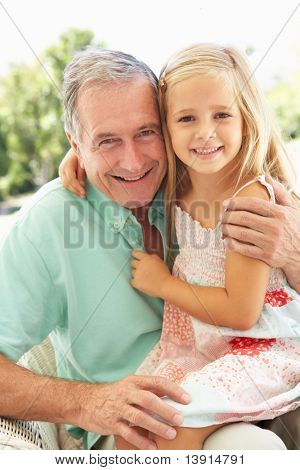 Portrait Of Grandfather With Granddaughter Relaxing Together On Sofa