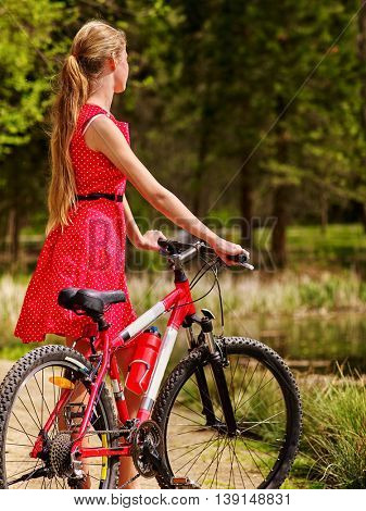 Bikes bicycling girl. Girl wearing red polka dots dress rides bicycle into park have rest. Girl in ecotourism. Bicycling is good for health. Cyclist look away. Back view.
