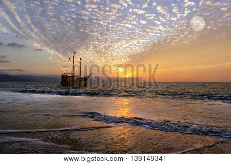 Pirate ship moon is an old antique ship out at sea with full flags flying as the sun sets on the ocean horizon and the full moon rises in the cloud filled sky.