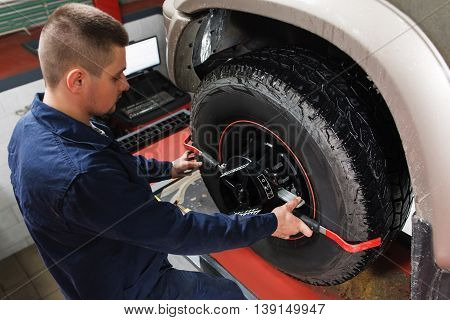 Mechanic tuning aligner for wheel alignment in garage closeup. Professional car maintenance in modern workshop