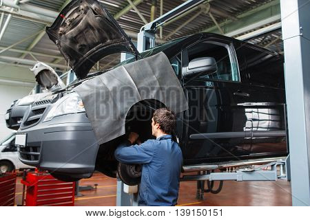 Serviceman checking brake system in car at garage. Disassembled automobile maintenance in repair shop.