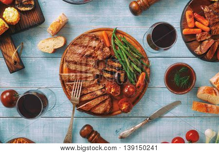 Juicy steak grilled with different grilled vegetables and red wine on blue wooden table top view