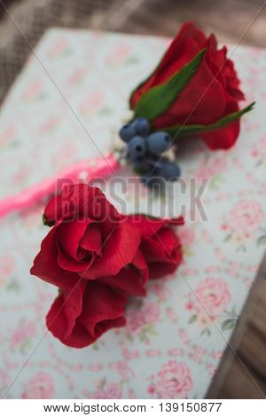 boutonniere and pins with artificial red rose