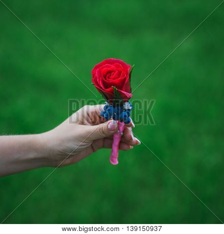 boutonniere with an artificial rose in hand