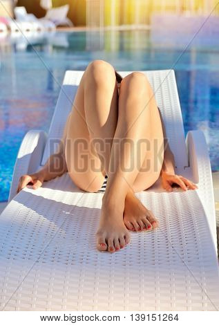 Young Woman Lying On A Lounger Near The Swimming Pool. Sunbathing Woman
