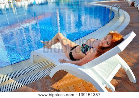 Leisure Time. Beautiful Young Woman Lying On The Deck Chair Near The Pool