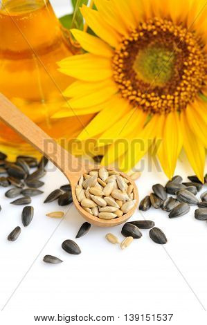 Wooden Spoon With Sunflower Seeds On A Background Of Flowers And A Bottle Of Oil