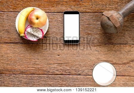 Smart phoneIron dumbbell and milk with fruit (bananaappkedragon fruit) on wooden floor.Top view focus.