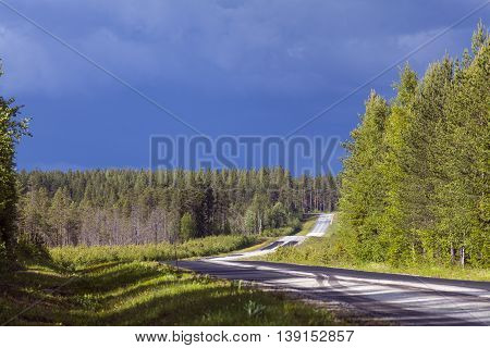 Country road in rural countryside. Heavy showers in the background.