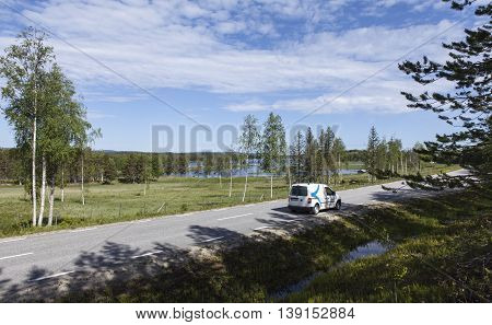 LAPLAND, SWEDEN ON JUNE 15. View of the countryside, highway and a car on June 15, 2016. River and meadows in the background. Editorial use.